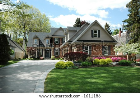 Red brick house with black shutters and pretty manicured lawn / garden - stock photo