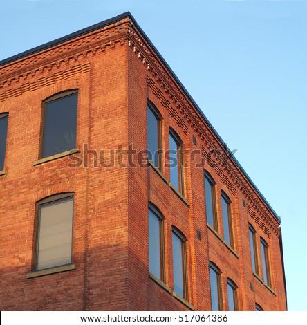 red brick office building corner in sunlight blue sky