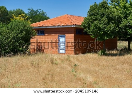 red brick shed with white wooden door protected by blue metal grate door with weeds in the foreground Zdjęcia stock ©