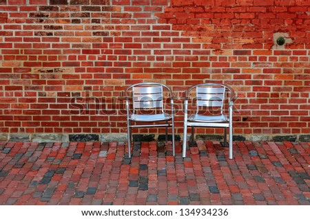 Red Brick Wall and Two Metal Chairs