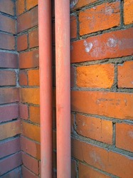 Red brick wall background. Two vertical pipes in the corner of an old house. Housing and communal services concept. Construction industry. Building facade. Copy space. Grunge dirty textured surface.