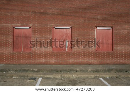 red brick wall boarded windows in parking lot