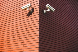 Red brick wall corner with video camera security system