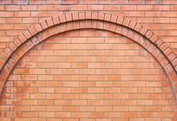 Red brick wall. Empty background of a rounded brick masonry arch. The surface of the cleaned brickwork texture.