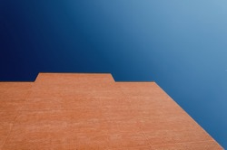 Red brick wall of a modern building against bright blue, clear sky on a sunny day. Copy space.