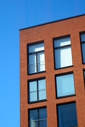 Red brick wall of a modern building against bright blue, clear sky on a sunny day. . High quality photo