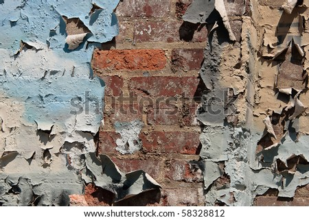 Red brick wall with heavy peeling paint in blue, white and grey