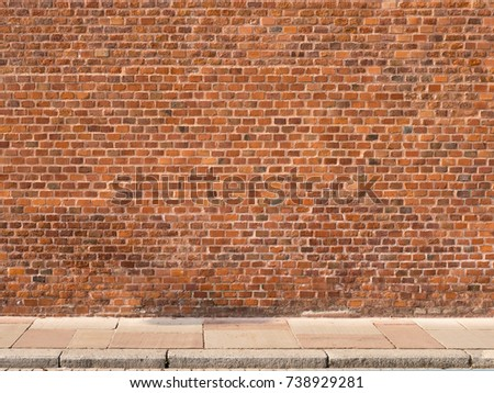 Red brick wall with sidewalk