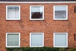 Red brick wall with square windows closed with white louvers, European living house facade, background texture