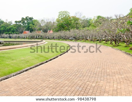 Red brick way in the garden after rain. - stock photo