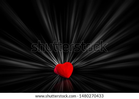 Red bright heart with brightly white rays  is on the black table/background. There is reflection too. World Kindness Day.