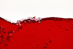 red bright liquid with wave and bubbles isolated on white