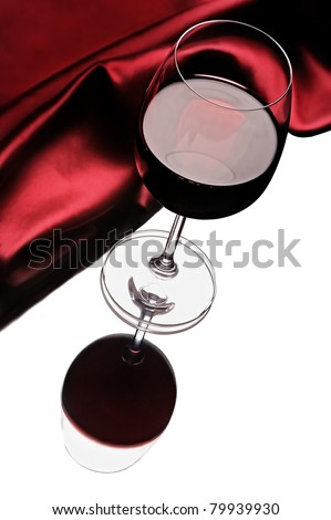 Red brilliant cloth and wine glass of red wine, reflected in mirror. - stock photo