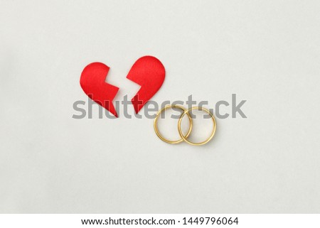 red broken heart split in two pieces with golden wedding rings, top view, flat lay, divorce and breakup concept #1449796064