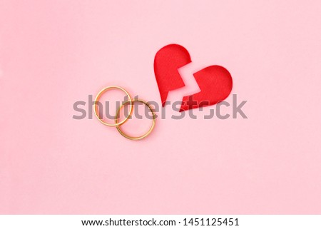 red broken heart split in two pieces with pair of golden wedding rings on pink background, top view, flat lay, divorce and breakup concept #1451125451