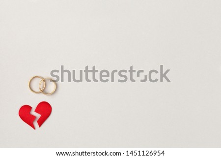red broken heart split in two pieces with pair of golden wedding rings, top view, flat lay, divorce and breakup concept, copy space #1451126954
