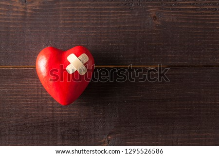 Red broken heart with a band-aid on a wooden background