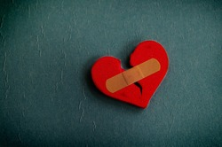 red broken heart with a bandage, on textured blue