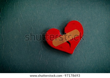 red broken heart with a bandage, on textured blue - stock photo