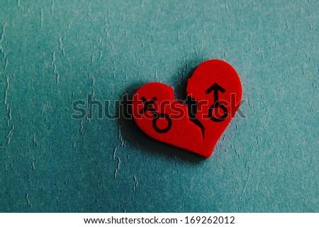 red broken heart with gender symbols, closeup on blue