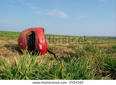 Red broken helmet  on an agricultural field