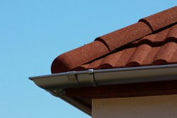 red brown color sandy textured modern concrete roof tile closeup detail with half round ridge tiles. light gray silver shallow zink rain gutter. house construction concept. light blue sky background