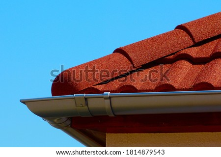 red brown color sandy textured modern concrete roof tile closeup detail with half round ridge tiles. light gray silver shallow zink gutter. house construction concept. light blue sky background.   Stock photo ©