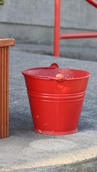 Red Bucket outside on the Concrete Floor