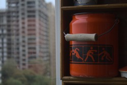 red bucket with pictograms of athletes on the windowsill in front of the new building