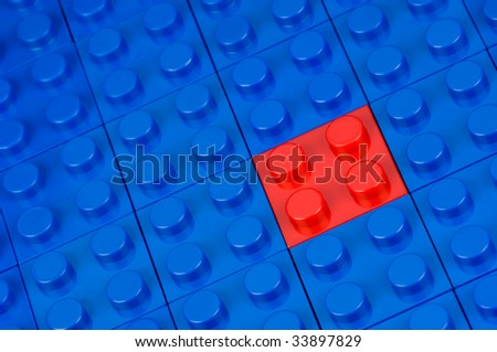 Red building block, fitted in blue ones