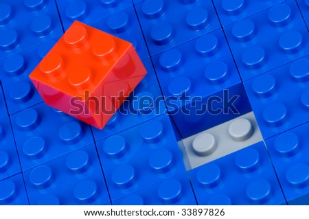 Red building block, ready to place into blue ones