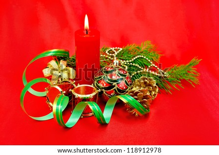 Red burning candle, Christmas tree decorations in the form of a ball, a hand bell with a bow, a drum, cones against red silk