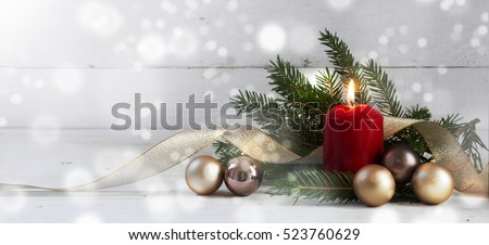 Red burning candle with christmas decoration, fir tree, baubles and ribbon, in front of a white  wooden wall with bokeh lights and generous copy space, panorama, selective focus, narrow depth of field #523760629