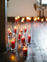red burning candles in glass vases on a wooden floor. muffled light. dark room