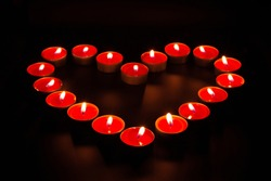 Red burning candles in the shape of a heart on a black background.