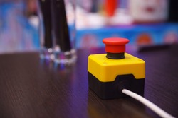Red button with a yellow stand on a dark table