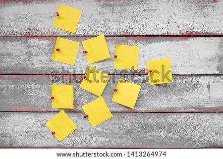 red buttons attached to the wooden boards leaflets for notes