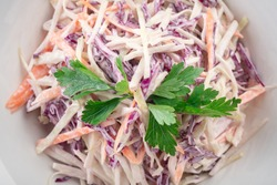Red cabbage and carrot fresh salad in a white plate, vegan healthy dish, top view