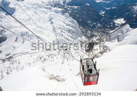 Red cabelway in the sunny Dolomites in a winter landscape