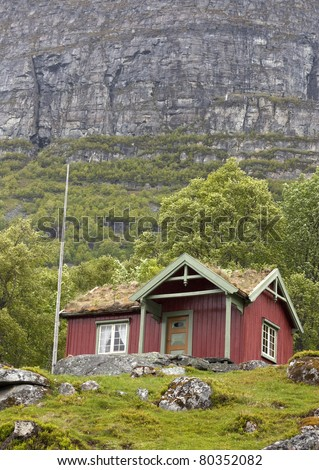 Red cabin with turf roof against a steep mountain cliff