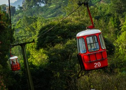 Red cable cars (Gondola) way to up hill with green trees and mountain in background