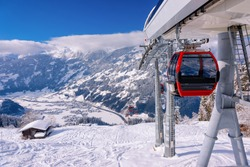 Red Cable cars of Zillertal Arena ski resort in Tyrol in Mayrhofen in Austria at winter Alps. Chair lifts in Alpine mountains with white snow and blue sky. Downhill fun at Austrian snowy slopes.