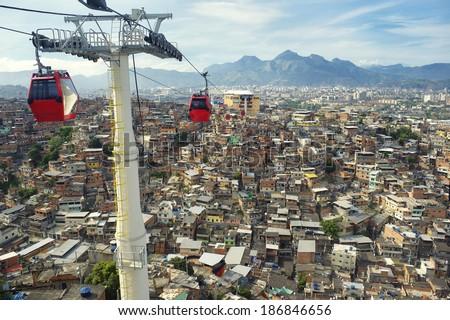 Red cable cars travel above Rio de Janeiro favela Complexo Alemao