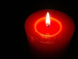 red candle burning in the dark