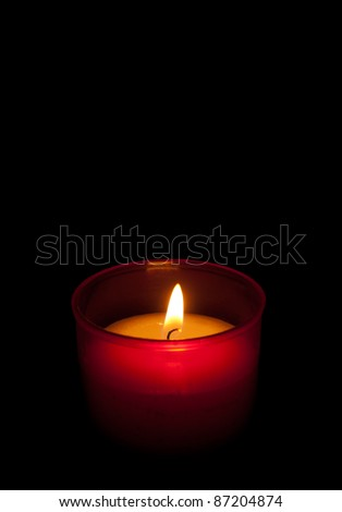 Red candle burning in the dark, black background - Christmas or general use