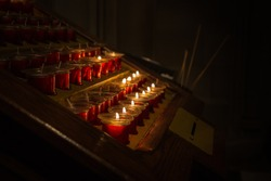 Red candle holdings with lighted up candles in a church.