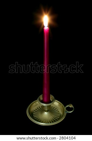 Red candle in a brass holder with glow from the flame.