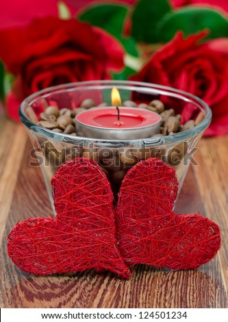 red candle in a glass cup with coffee beans and two hearts for Valentine's Day closeup
