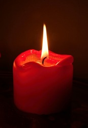 Red candle in front of a black background