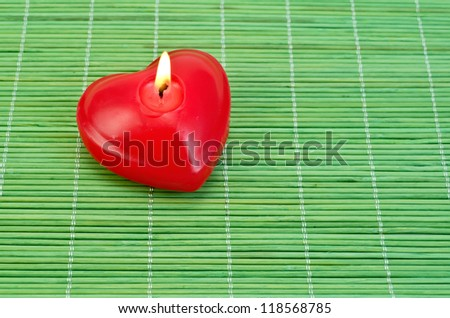 Red candle in the shape of a heart on a green bamboo mat